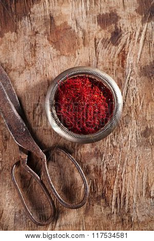 saffron spice in vintage bowl on old wood background, closeup
