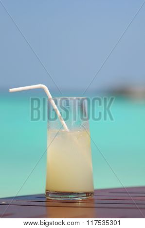 Glass With Light Coctail And Staw With Blue Lagoon Background