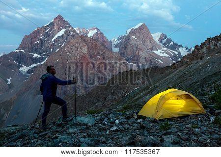 Hiker walking toward illuminated climbing tent