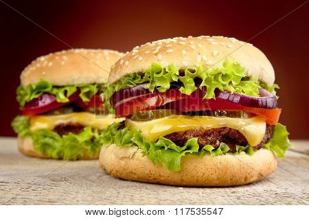 Cheeseburgers On Wooden Table On Burned Background