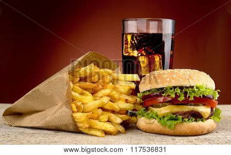 Cheeseburger With Drink Of Cola, French Fries On Red Spotligh