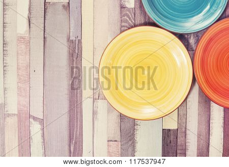 ?olored Plates On The Wooden Background