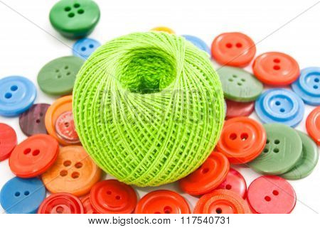 Green Ball Of Thread And Buttons On White