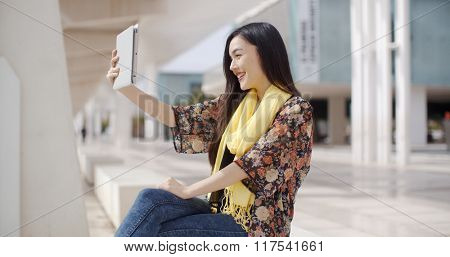 Woman taking a self portrait with tablet