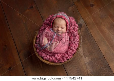 Smiling Newborn Girl Sleeping In Wooden Bowl