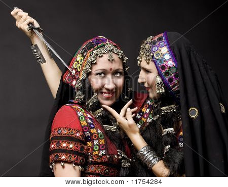 two young woman play with knife