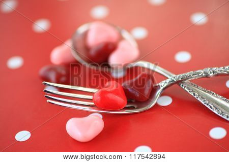 Valentine candy hearts on fork and spoon
