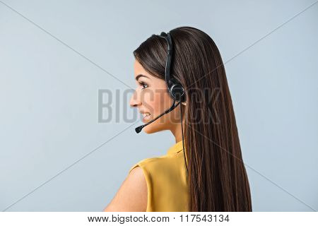 Photo of beautiful young call center operator standing near gray background. Woman with headphones smiling