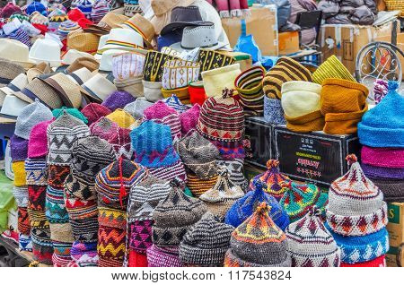 MARRAKESH, MOROCCO, APRIL 3, 2015:  Local sellers offer hats and other souvenirs on street stands in souks