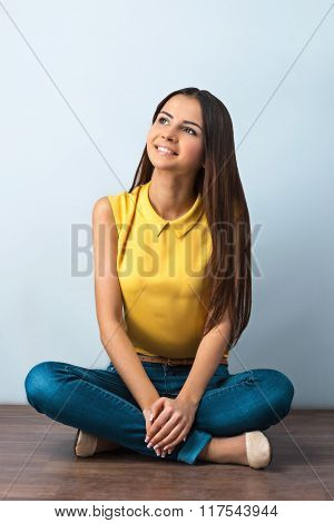 Photo of beautiful young business woman sitting on wooden floor. Smiling woman looking up
