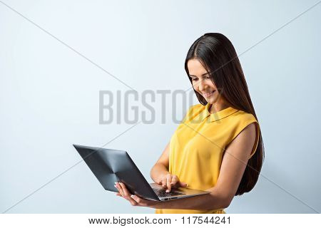Photo of beautiful young business woman standing near gray background. Smiling woman with yellow shirt using laptop