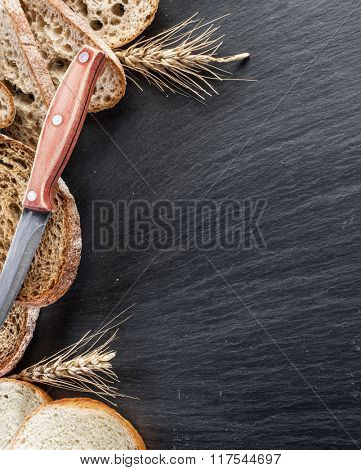 Bread slices, a wheat and a knife on the black stone desk.