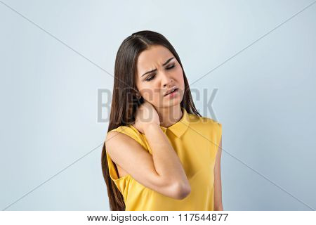 Photo of beautiful young business woman standing near gray background. Woman with yellow shirt having neckache