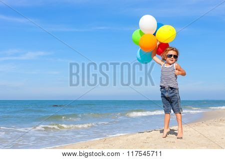 Little Boy With Balloons Standing On The Beach