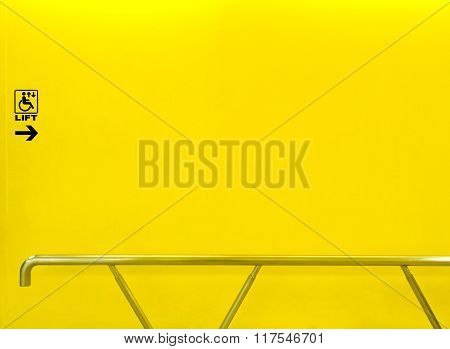 Lift Sign For Disabled On Yellow Wall With Handrail
