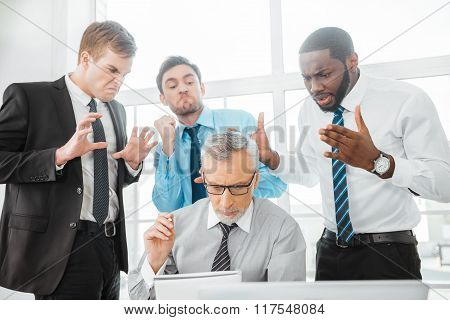 Photo of aged boss and his colleagues. Businessmen working in office with big window. Man using laptop. Angry and unhappy subordinates standing behind boss