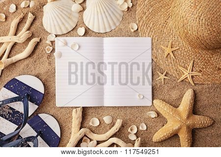 beach accessories on sand and empty notebook