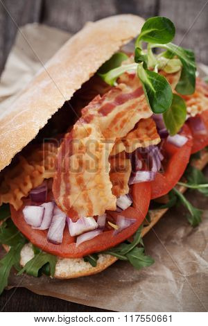 Sandwich with fried bacon, tomato and onion