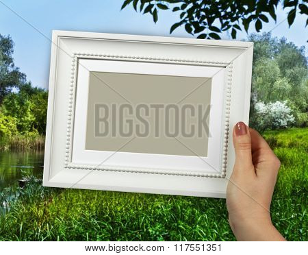Wooden frame in beautiful woman hands on the countryside scene background
