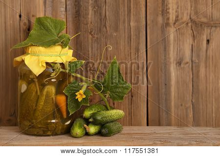 Homemade salted cucumbers in glass jar fresh cucumbers. Jar of canned cucumbers on wooden background