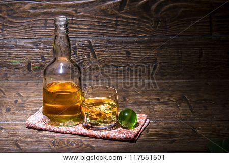 Bottle With A Glass Whiskey And Green Ball Are On The Napkin