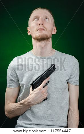 Firearms And Murderer Topic: Suicide In A Gray T-shirt Holding A Gun On A Dark Green Background