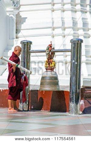 YANGON, MYANMAR - NOVEMBER 25, 2015 - Buddhist monk ringing the bell in the Shwedagon Pagoda on November 25, 2015 in Yangon. The Pagoda is the most famous buddhist temple in Myanmar.