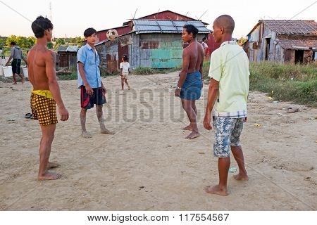 YANGON, MYANMAR - November 25, 2015: Young guys playing football in the countryside from Myanmar