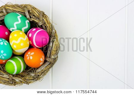 Spring nest close up with Easter Eggs against white wood