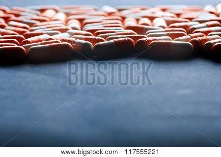Many orange capsules on black background