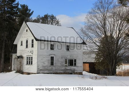 A farm house and barn in winter next to a Lake
