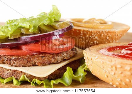 Traditional American Cheeseburger. Meat, Bun And Vegetables Close Up