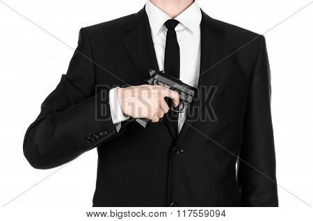 Firearms And Security Topic: A Man In A Black Suit Holding A Gun On An Isolated White Background In