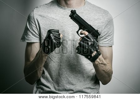 Horror And Firearms Topic: The Killer With A Gun In His Hand In Black Gloves On A Gray Background In