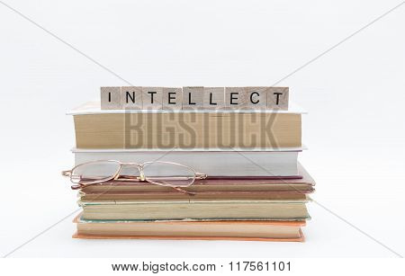 Small old stack of books with reading glasses and message word at the top