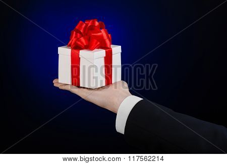 The Theme Of Celebrations And Gifts: A Man In A Black Suit Holding A Exclusive Gift Wrapped In White