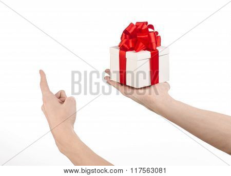 The Theme Of Celebrations And Gifts: Hand Holding A Gift Wrapped In White Box With Red Ribbon And Bo