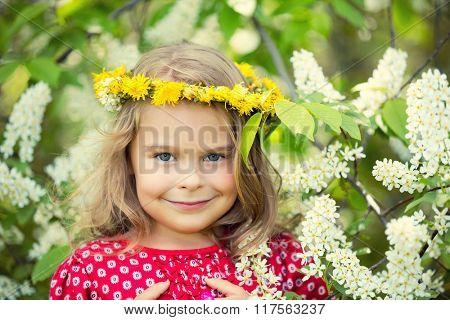 Portrait of happy little girl in spring flowers