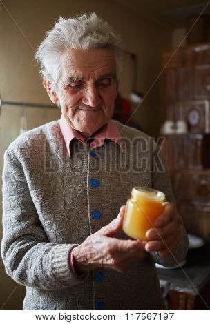 Old Man Holding A Jar Of Honey
