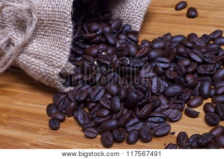 Sack Of Coffee Grains On Wood Background