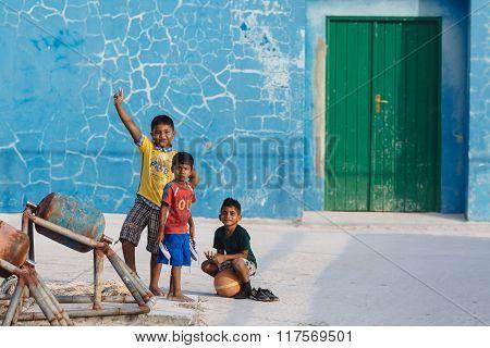 MAAFUSHI, MALDIVES-JANUARY 5, 2013:Three barefooted Maldivian kids attracts photographer's attention