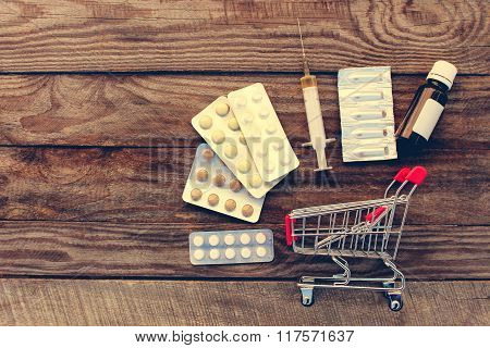 Shopping cart with pills, a syringe, candles on the old wood background. Toned image.