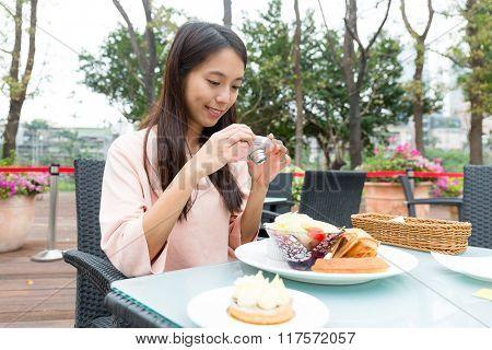 Woman taking a photo of breakfast