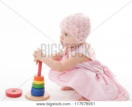 little child baby girl in pink dress playing with pyramid isolated on white studio shot