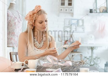 Young woman sitting at table at home, doing creative works, with ribbon and branches.