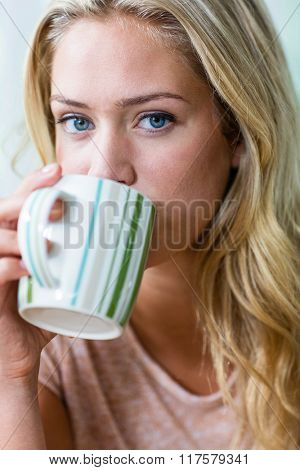 Pretty blonde woman drinking tea in the kitchen