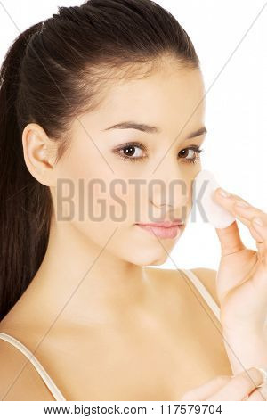 Beautiful woman cleaning make up.