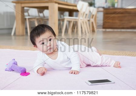 Cute baby on the carpet looking at the camera