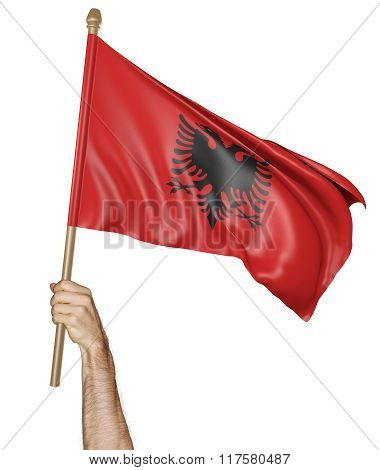 Hand proudly waving the national flag of Albania
