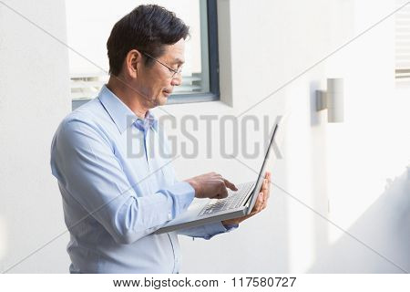 Concentrated man using laptop at home